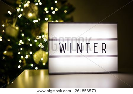 Winter And Christmas Concept - Lihtbox With Winter Word In Dark Room With Decorated Christmas Tree