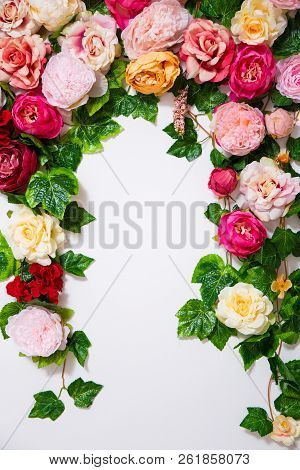 Summer Background - Close Up Of Colorful Artificial Flowers Over White Wall With Copy Space