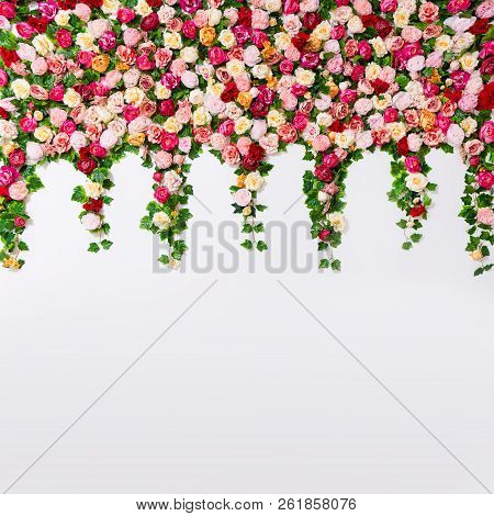 Spring And Summer Background - Close Up Of Colorful Composition Of Artificial Flowers Over White Wal