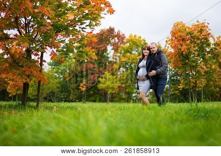 Portrait Of Happy Pregnant Woman And Her Husband Posing In Autumn Park