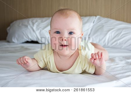 Portrait Of Cute Little Baby Lying On The Bed