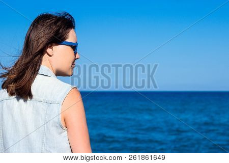 Summer And Travel Concept - Back View Of Young Woman Over Beach Background
