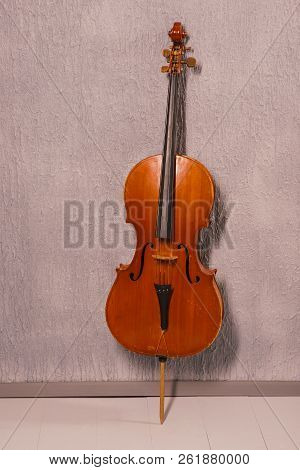 Old Battered Cello Standing Near A Gray Textured Wall.