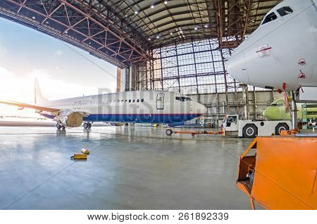Passenger Plane With A Damaged Engine Is Push Roll Up Tow Tractor To The Hangar For Repair, Maintena