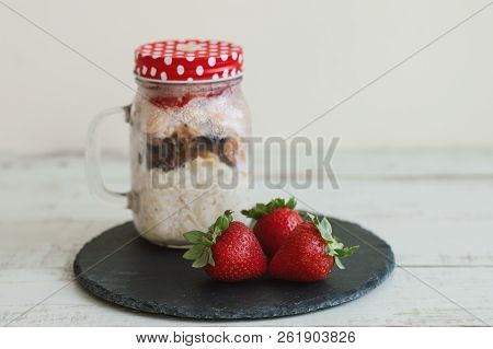 Fresh Strawberry And Overnight Oats With Milk, Nuts And Berries In A Jar. Breakfast Recipe