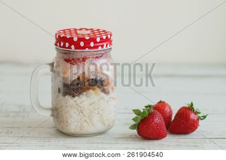 Homemade Overnight Oats With Strawberry, Milk, Dried Fruits And Nuts In A Glass Jar. Breakfast Meal