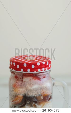 Overnight Oats With Mix Of Berries, Nuts, Milk And Fruits In A Glass Jar, Vertical Photo, Copy Space