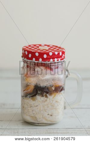 Homemade Overnight Oats With Milk, Berries, Dried Fruits And Nuts On Wooden Table. Quick And Simple