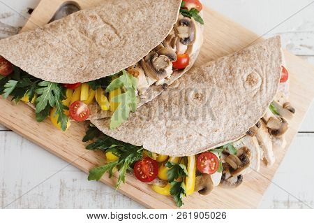 Two Sandwiches With Whole Wheat Wrap, Chicken Breast, Mushroom And Seasonal Vegetables Served On Woo