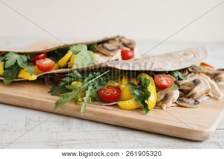 Wraps With Chicken, Mushroom, Cherry Tomato, Capsicum, Fresh Arugula And Parsley Leaves Served On Wo