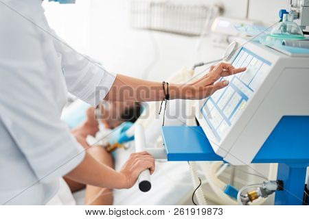 Female Doctor Touching Monitor Of Mechanical Ventilator