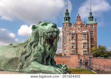 Tower spires over lion bronze sculpture guard at the entrance of Rosenborg Castle, built in 17th century. Historical landmarks of Copenhagen, Denmark. poster