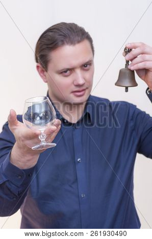 Portrait Of Young Caucasian Ethnicity Man Ringing A Small Bell In One Hand Calling For Service With