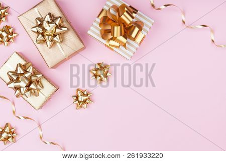 Fashion Gifts Or Presents Boxes With Golden Bows On Pink Pastel Background Top View. Flat Lay Compos