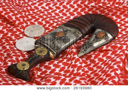 A traditional Arab dagger or khanjar, keffiyah headdress and Maria Theresia taler silver coins. poster