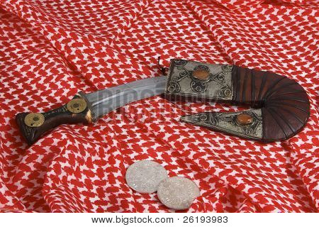 A traditional Arab dagger or khanjar, keffiyah headdress and Maria Theresia taler silver coins.