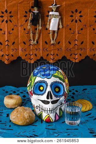 Styrofoam Skull With Flowers And Mustache In A Day Of The Dead Offering Altar With Little Skeletons