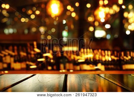 Top Of Wood Table With Blur Bottle Of Alcohol Drinking For Dark Night Party And Colorful Light Of Pu
