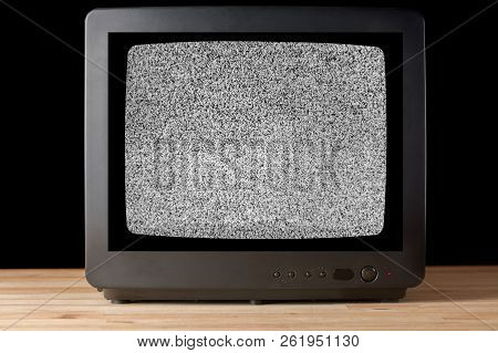 Old Vintage Tv Set Televisor On Wooden Table Againt Black Background With No Signal Television Grain