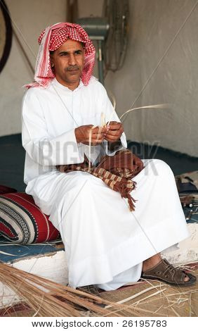 A Gulf Arab craftsman making small objects from dried reeds at the Doha Cultural festival. The focus is on the hands, face is slightly soft at full size.