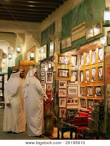Qatari nationals admire old photos of prominent local people at a shop in Doha's Old Souq.