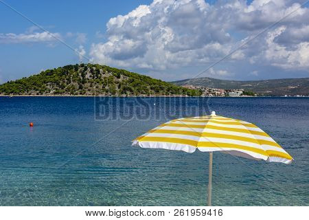 White And Yellow Sun Umbrella On Coast Od Adriatic Sea. Summer Holiday In Croatia.