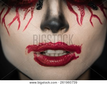 Makeup for Halloween. Scary lips in the blood and crooked teeth.