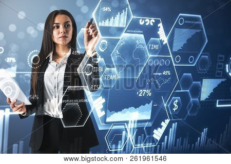 Attractive Young European Businesswoman Using Digital Business Interface On Blue Background. Future