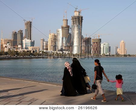 Covered Qatari women with their children and housemaid strolling on the Corniche in Doha, Spring 2008, with the New District construction work taking place across the Doha Bay.
