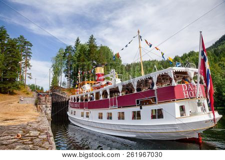 EIDSFOSS, NORWAY - JULY 18, 2018: M/S Henrik Ibsen ferry boat entering lock chamber at the Eidsfoss lock during a unique historical boat trip through spectacular Norwegian nature by the Telemark Canal