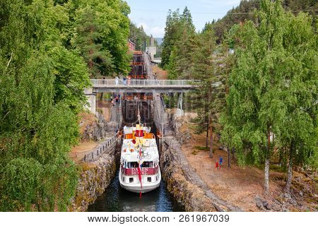 ULEFOSS, NORWAY - JULY 18, 2018: M/S Henrik Ibsen ferry boat entering lock chamber at the Vrangfoss staircase locks during a boat trip through spectacular Norwegian nature by the Telemark Canal