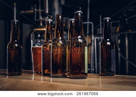 Bottles And Glass Of Craft Beer On Wooden Bar Counter At The Indie Brewery.