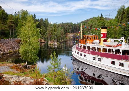 ULEFOSS, NORWAY - JULY 18, 2018: M/S Henrik Ibsen ferry boat entering lower canal of the Vrangfoss lock during a unique historical boat trip through spectacular Norwegian nature by the Telemark Canal