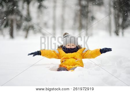 Cute Little Boy Having Fun In The Snow During A Snowfall. Outdoor Winter Activities For Family With