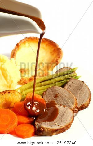 A meal of roast beef with carrots, Yorkshire puddings, potatoes and asparagus, with gravy being poured on