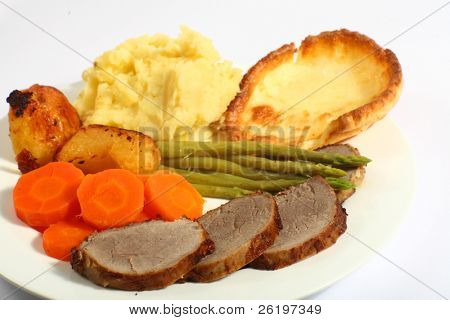 A meal of roast beef with carrots, mashed potatoes, asparagus and Yorkshire pudding.