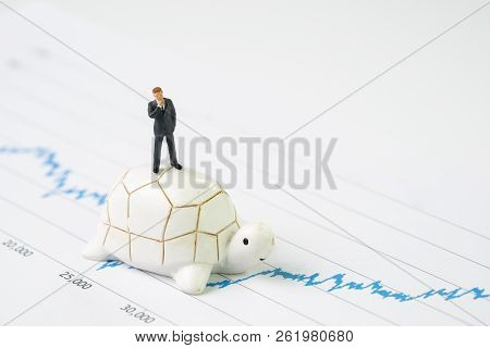 Invest With Slow But Steady For Long Term Success Metaphor, Miniature People Businessman Riding Turt