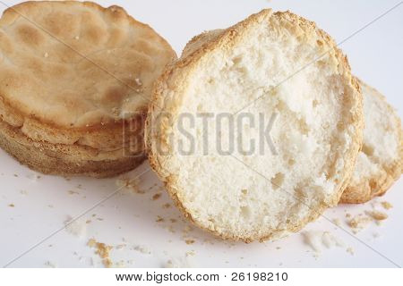 Two crumbly, gluten-free bread rolls, one sliced, over a white background
