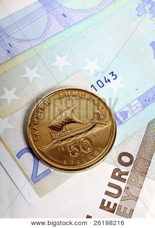 A fifty drachma coin lying on euro notes which replaced the Greek currency. Greece's economic woes are now seen as a threat to the stability of the euro.