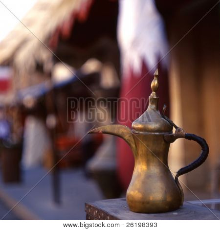 A coffee pot - the Arab symbol of welcome - in front of a Qatari flag in Souq Waqif, Doha, Qatar. The souq is one of Qatar's main tourist attractions. poster