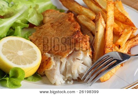 A dinner of fish and chips (or french fries) served with a salad of garden-fresh lettuce, rocket and tomato and a piece of lemon