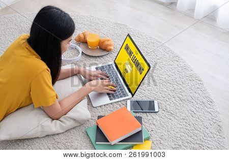 Asian Female Student  Log On To E-learing Website On Laptop Computer At Home.woman Lying Down On Car