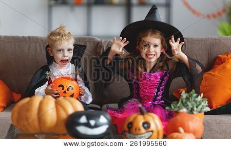 Happy Children In Costumes Of Witch And Vampire  Preparing The Home For Holiday Halloween