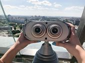 Viewing stationary binoculars against a white-blue sky. Gray binoculars on the viewing platform at height in the hands of a girl with multi-colored nails. From the roof overlooking the beautiful city. poster