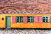 Colorful walls in traditional style house in Copenhagen, Denmark. Facade of historical brick building with tile roof. poster