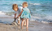two children playing on sand beach poster