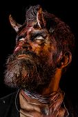 Halloween holiday celebration, cosplay. Satan with beard, red blood, wounds roll eyes on face. Demon with bloody horns on head. Man devil on black background. Hell, death, evil, horror concept. poster