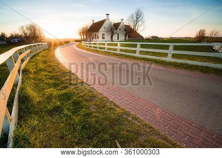 Dutch Landscape With Historical Houses In Evening Along A Curved Road With White Fence In The Countr