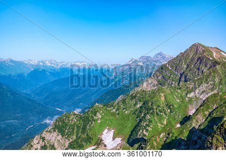 Mountain Range With Rocks And Trees Against A Clear Blue Sky. Non-melted Snow In The Summer On A Mou