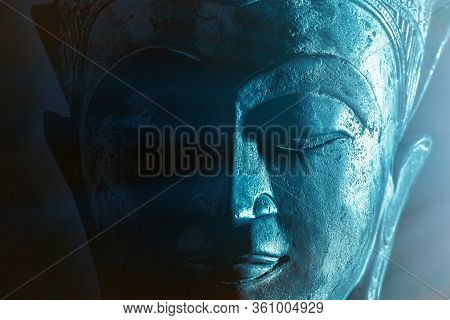 Spiritual Enlightenment. Mindful Buddha Face Close-up With Ethereal Blue Light. Mysticism And Spirit